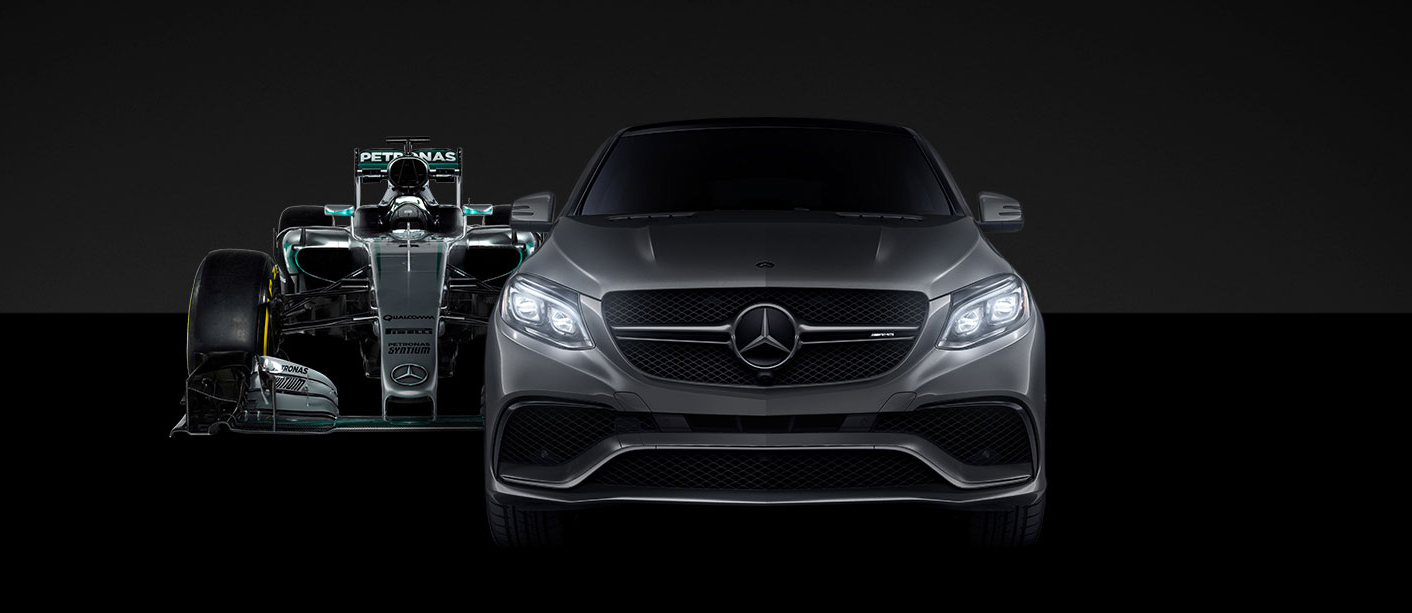 Front view of a dark grey GLE with an f1 race car behind it