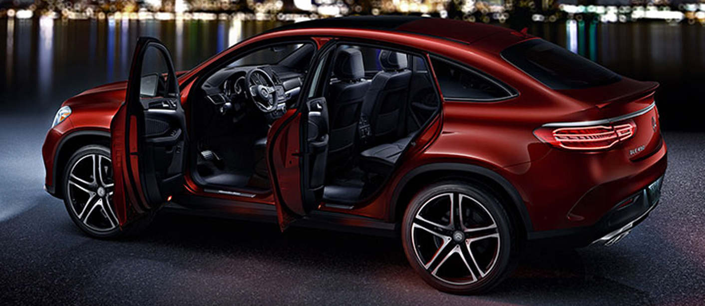 Driver's side view of a red GLE Coupe SUV with front and back door open