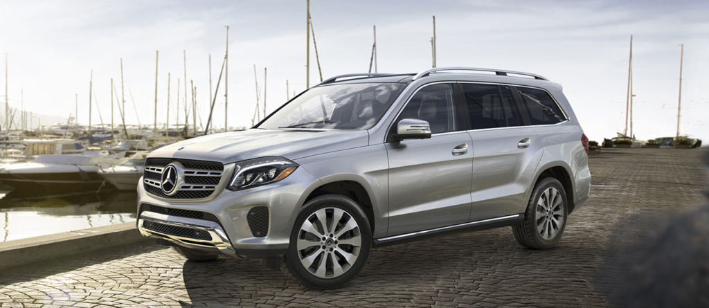Silver 2019 GLS SUV parked beside a boat dock
