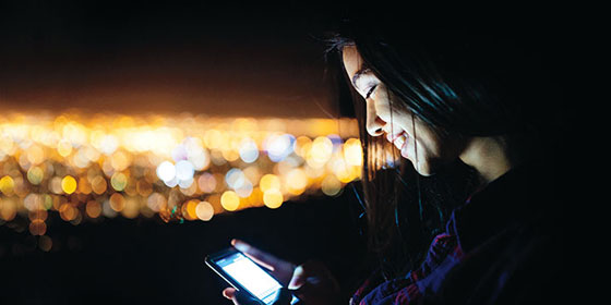 Woman Looking at her phone at night