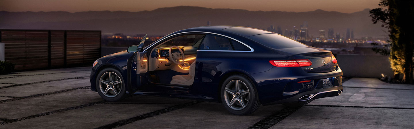 3/4 rear view of E-class coupe with driver side door open showing interior design